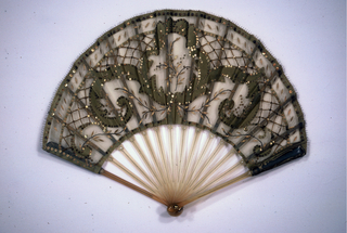 Pleated fan. Arch-shaped leaf of green net applied with green silk and gold metallic spangles in a variety of shapes. Blond horn sticks incised and painted with simple flower design. Painted wood slips. Metal bail and paste jewels at rivet.