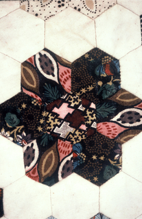 Unfinished patchwork quilt top with a design of hexagons arranged as flowers on a white ground. Some of the fabrics are English block prints from the 1780s and 1790s; others are 19th century roller-printed fabrics. The hexagonal shapes were formed over paper patterns, still present.