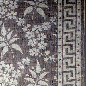 Length of damask used to protect carpeting on stairs during summer. Pattern of offset leaves with berries framed by flowers forming a lattice. This pattern fills the 42.5 cm (16 3/4 in.) central section. Border on both sides, mirror images of each other, 7.5 cm (3 in.) wide with simple fret and dotted guards. Brown warp and ivory weft.