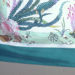 Square scarf with an acqua border and off-white field filled with underwater life: plants and coral, fish, crab, turtle, starfish, shells, anemones, pearls, etc. In soft blues, greens, yellows, and pinks.