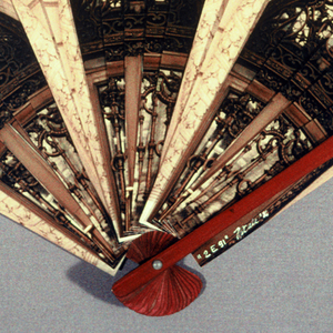 Brisé fan. Strips of a photographic image individually taped to red stained bamboo sticks. Obverse: the facade of the Cooper-Hewitt Museum.