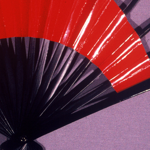 Pleated fan. Double leaf: front and back, asymmetrical leaves of glazed red paper exposing an increasing amount of stick from right to left. Black lacquered bamboo wood sticks.