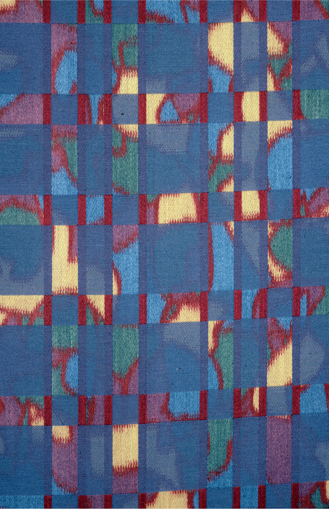 Reversible fabric with a grid of squares and rectangles, alternating blue and a random pattern in blue, yellow, red and green.