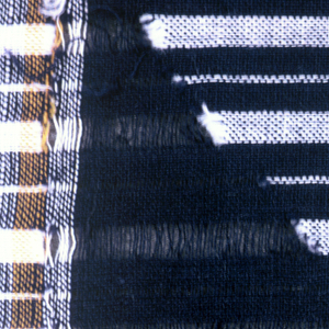 Wrapper of fine cotton with a center panel and a wide border on each long side. The center panel has a small blue and white check with white threads withdrawn in a pattern of concentric diamonds. The borders have blue and white stripes with white threads withdrawn in a pattern of rotated triangles. With three narrow yellow stripes in each border.