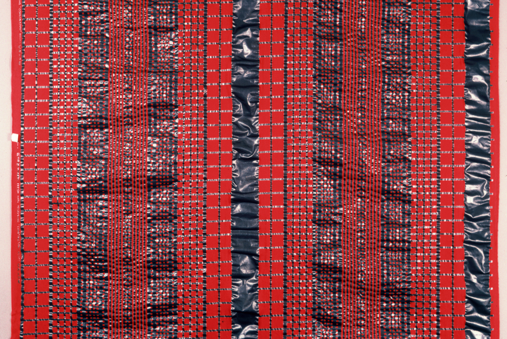 Red fabric with grid design in metallic grey, exaggerated seersucker effect