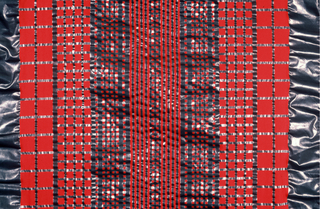 Red fabric with grid design in metallic grey, exaggerated seersucker effect