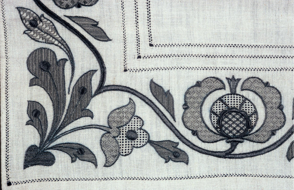 Table cover with an embroidered border of curving vines with flowers embroidered in sage green. Design is the same on each of the four edges.