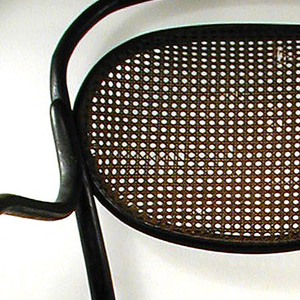 Oblong, rounded upper frame and circular seat frame superimposed to a circular stretcher.  Long, curved armrails depart from seat back and loop around in air to connect to the seat frame.  Another bent wood half-loop emulates the shape and direction of the top of the seat back.  Legs taper, with back legs pointing outwards more drastically as they meet the floor.