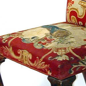 Simple cabriole legs ending in club feet; tall back rounded at top; seat and back upholstered in tapestry of red ground decorated with scrollwork and vase of flowers in cartouche in tones of cream, tan, ochre and green.  Chairs -1a, -1b and -1d with fitted covers of green fabric. 1a- Needle point of large bouquet of flowers on seat 1b- Needle point of bird on seat 1c- Needle point of small bouquet of flowers on seat 1d- Needle point of small bouquet of flowers on seat