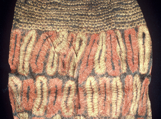A woman's ceremonial skirt in tubular form made from woven raffia. Patterned by tied resist dying in ocher, red, and dark brown. The main body has four rows of red and ochre lozenges, there is an open-work section in the upper quarter. The upper edge is finished with an edging, and the bottom with a knotted fringe.