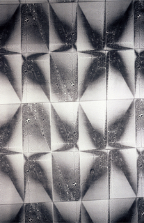 Silvery shapes causing optical confusion in a grid.