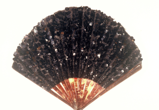 Pleated fan. Black silk net leaf embroidered all over with small and large black sequins. Faux tortoise shell sticks. Metal bail at rivet.
