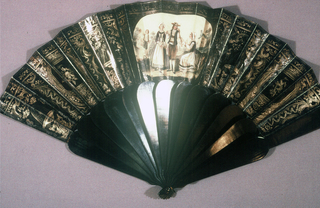 Pleated fan. Printed paper leaf with cartouche enclosing a rustic dutch scene surrounded by  embossed ornament on a black ground. Black painted wood sticks.
