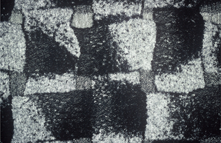 Length of woven fabric with various textures and design of interlocking blocks in black shading to grey.