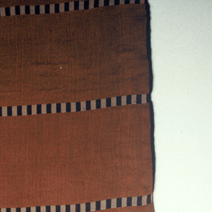 Length of woven fabric with horizontal stripes that are vertically striped black and white, on a rust-brown ground.