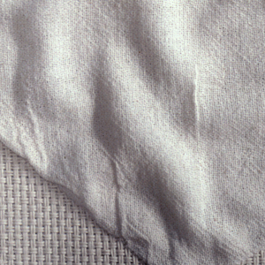 Length of woven cotton with white-on-white design of geometric shapes formed in plain weave variations.