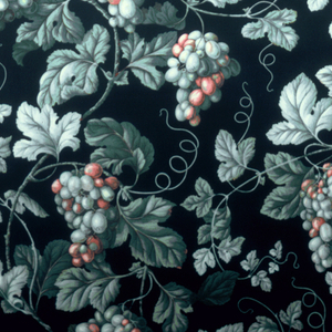 Curving grapevines with leaves and fruit in greens, brown and pink on a black background. Glazed.