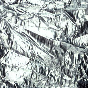 """Silver colored fabric with areas which are tied and """"melted off"""" to leave sheer nylon."""
