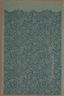 All-over dense pattern of foliage and stylized flowers. Printed in blue on lighter blue-green ground. This was the beginning of the roll, as along top edge, there is a space with no block printing, just the ground color.
