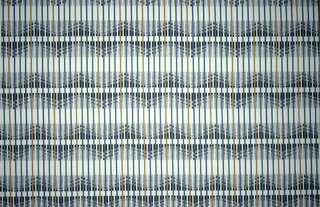 White fabric with narrow vertical stripes with horizontal bands of grey with black undulating zigzags.