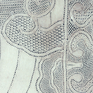 Table mat of ivory silk bobbin lace, with two fish with elaborate tails moving through bubbles and swirls. Border of shapes like Chinese cloud-collars.