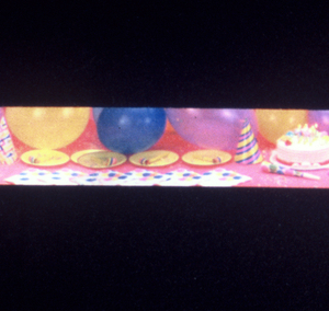 Ribbon on its cardboard roll. Design of balloons, party hats and paper plates.