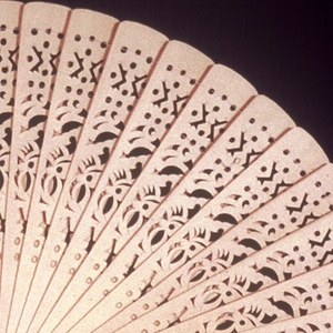 Large cockade fan with pierced bone sticks connected with string. Wooden handle and metal rivet.