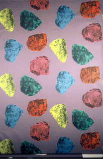On lavender ground, floating printed stone-like or natural materials in green, blue, yellow, pink, and red.