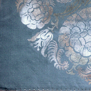 Steel blue silk pillow cover printed with silver and gold metallic pigments in a teardrop form filled with stylized floral forms.
