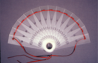 Brisé fan of translucent plastic. Sticks pierced with circles, red connecting ribbon and large plastic rivet.