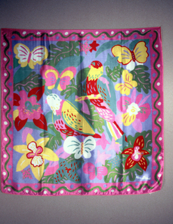 Scarf with bright pink edge and blue center that is printed with brightly colored birds, flowers, and butterfies.