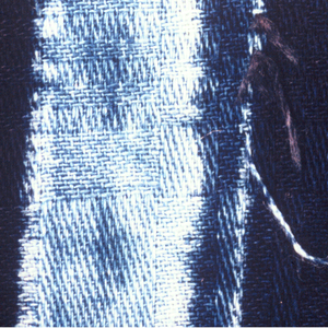 Length of cotton dyed deep indigo blue with horizontal bands of smooth and crimped line, reserved in pale blue by stitched resist technique.