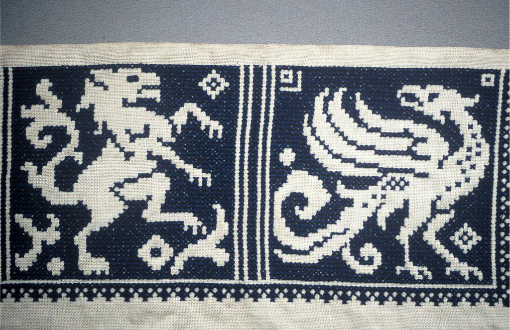 Sampler of cross stitch patterns, including heraldic animals and all over pattern worked in deep blue on natural color linen, fringed on sides and bottom.