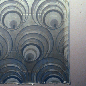 Blue and silver discs arranged in a repeating pattern.