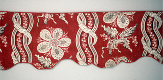 Shaped valance. Design of curving stripes with five-petaled flowers in the field. Red and black on white. Three seams across the width of the valance.
