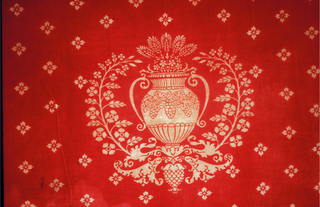 An urn surrounded by branches in a field of small rosettes.The red was printed on a yellow ground.