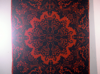Bold design of central medallion surrounded by a full border. In black on red.