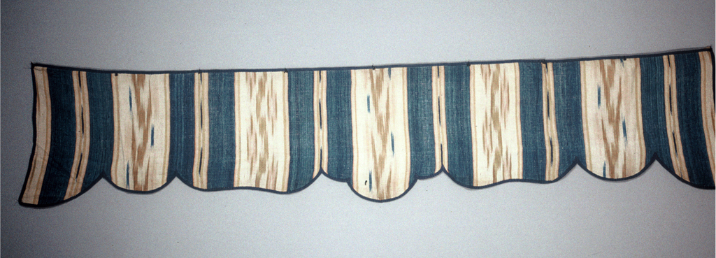 Wide valance with bands of solid blue and ochre, pink and beige weft ikat. Same fabric used as part of the facing on the back of the valance. valance is bound with plain weave tape.