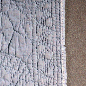 Trapunto cover the size of a crib quilt. Design of a basket of flowers in the center, a heart motif in each of the corners and a five pointed star on one side; an eight pointed star on the other side. Piece was originally white but had been dyed pale blue.