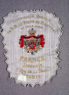 "Embroidered label with crest in center has red swags surmounted by a crown that frame two dragons holding another crown. Above in dark yellow thread: ""Fournisseur Brevete De S.M. La Reine de Portugal et de la cour."" At bottom in same thread: ""Franck Lingerie 7, Rue de la Paix. Paris"""
