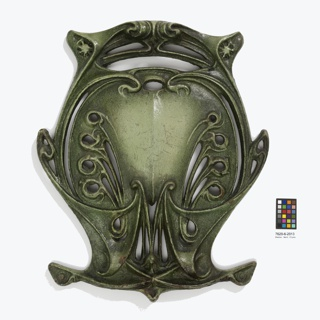 Green painted cast iron, shield-shaped medallion from the balustrade of an entrance into the Paris Metro, ornate openwork floral and whiplash motif.