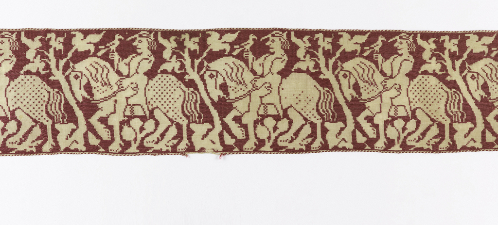 Linen band embroidered with red silk in long-legged cross stitches. Embroidery forms the background, leaving a design of a man on horseback with a falcon in the natural linen.