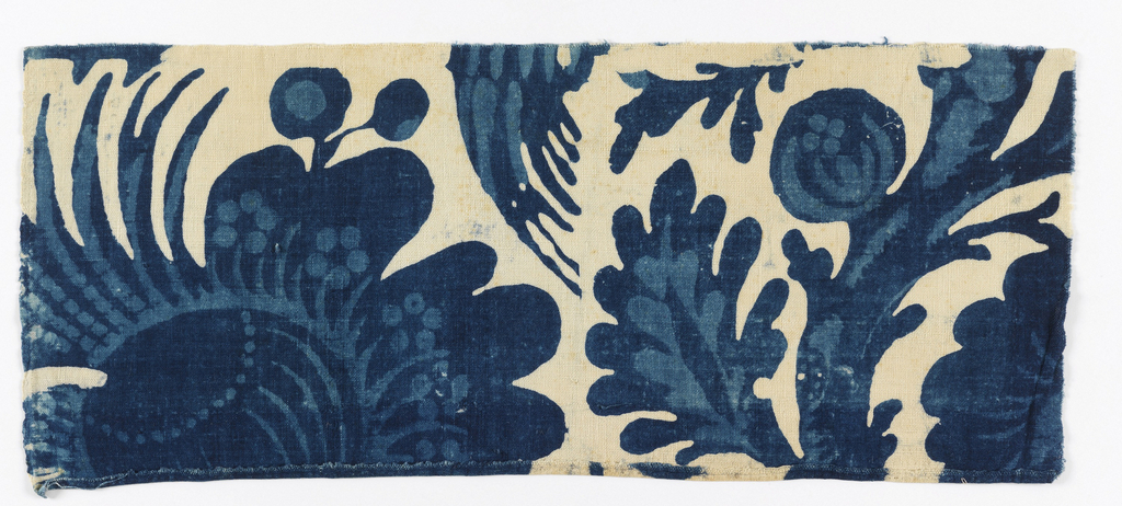 Cotton textile fragments with resist dye showing florals in two shades of blue on white background. Design, incomplete, shows bird in foliage, and large leaf and flower.