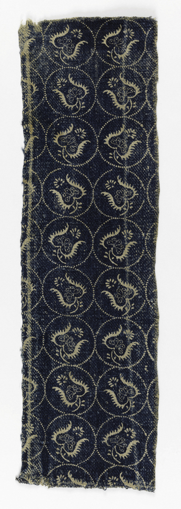 Blue resist on ivory in a pattern of blossoms in circles. A square pattern layout with pattern reversed in alternate rows. One unit is 3 inches high. Selvage on one side.