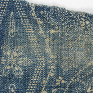 Textile fragment with  pattern of blue resist on ivory showing vertical diamonds alternating with floral vines. 2/2 twill weave.