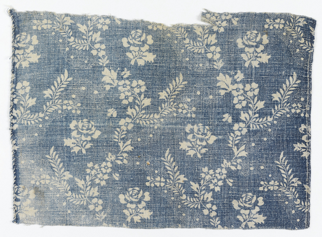 Textile with allover pattern of blue resist on ivory showing rows of curving floral branches in offset alignment. Selvage on one side.