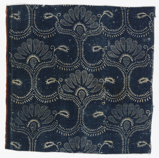 Textile with pattern of blue resist on ivory showing floral forms, one above the other, in a half drop pattern. Selvage on one side. Narrow red strip of fabric sewn onto selvage.