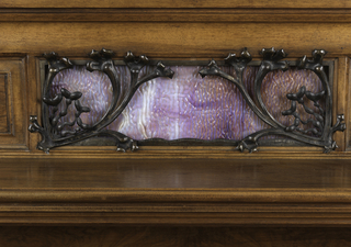 Walnut body, carved at several places to represent algae, consisting of two cabinets in the base, an open space under two drawers under a horizontal surface covered with a marble slab, all below an upper small wooden shelf backed by a vertical surface consisting of mottled colored glass representing the sea behind wrought iron in the form of seawood; gilded metal drawer pulls.