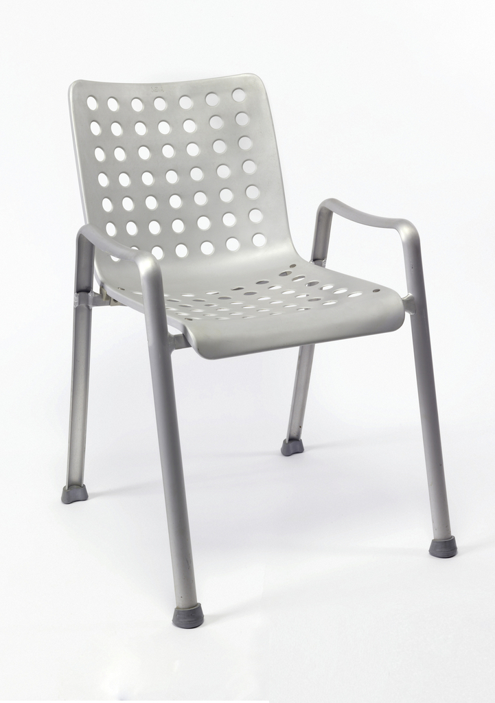 Stamped seat shell supported on a frame that functions as legs and armrests, the back is punched with 49 hand-cut holes, and the seat with 42; gray rubber feet.