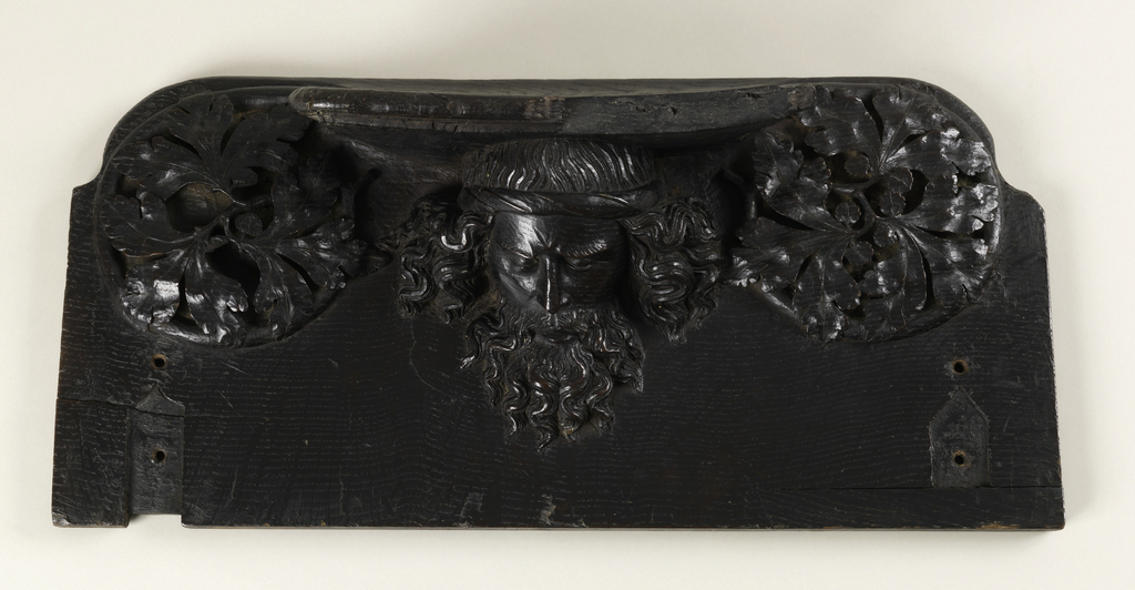 Two roughly rectangular choir seats, each carved on undersurface, with shallow rests supported by: a stooped figure of a bearded man flanked by foliate roundels (-1a); head of a bearded man with flowing hair, flanked by foliate roundles (-1b); each seat with indentations for hinges on lower left and right.